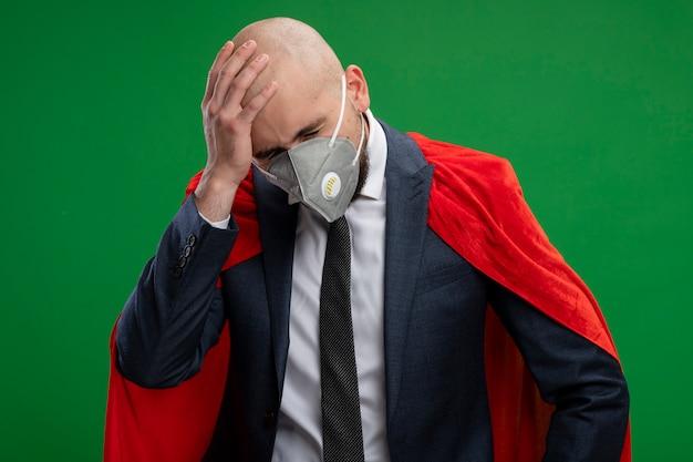 Uomo d'affari barbuto super eroe in mantello rosso e maschera facciale protettiva guardando in basso confuso con la mano sulla sua testa per errore in piedi sopra il muro verde