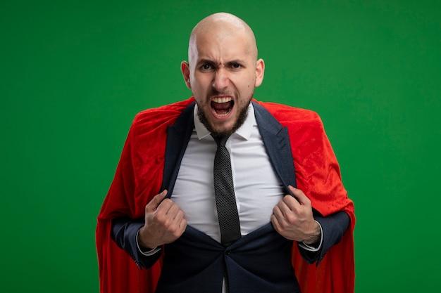 Uomo d'affari barbuto super eroe in mantello rosso che grida essendo eccitato e pronto a combattere in piedi sopra il muro verde