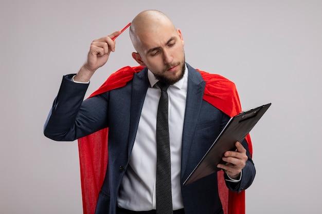 Uomo d'affari barbuto super eroe in mantello rosso che mostra appunti con pagine vuote guardando pagine grattandosi la testa con la penna in piedi sopra il muro bianco