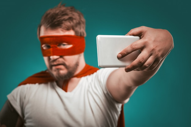 Super hero blogger man makes selfie photo or video on mobile phone