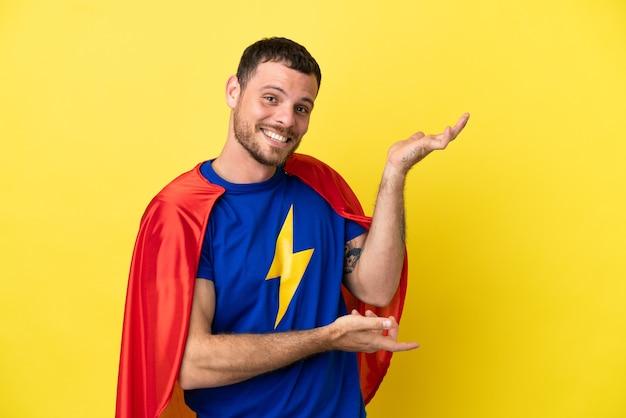 Супергерой бразильский мужчина изолирован на желтом фоне, протягивая руки в сторону, приглашая приехать