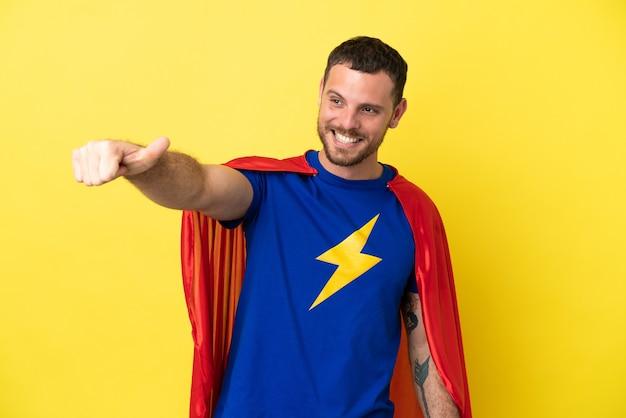 노란색 배경에 고립 된 슈퍼 영웅 브라질 남자 제스처를 엄지손가락을 포기
