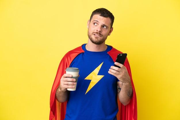 Супергерой бразильский мужчина изолирован на желтом фоне держит кофе на вынос и мобильный, думая о чем-то