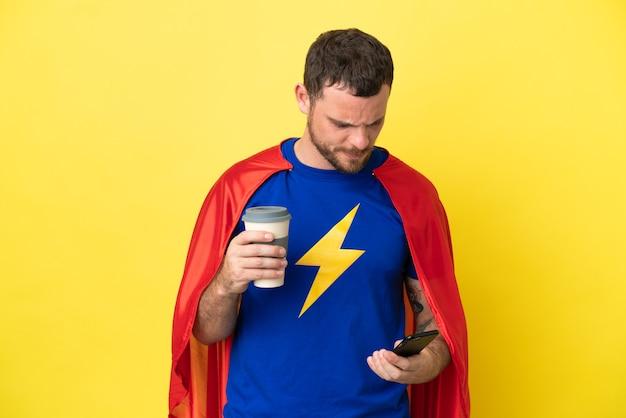 Супергерой бразильский мужчина, изолированные на желтом фоне, держит кофе на вынос и мобильный