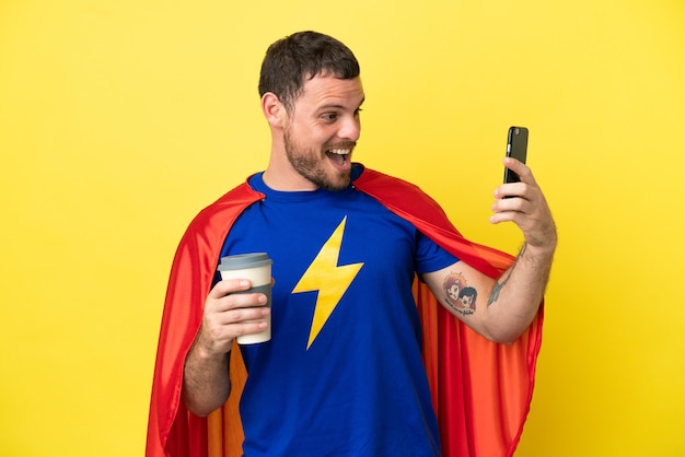 노란색 배경에 격리된 슈퍼 히어로 브라질 남자는 테이크아웃 커피와 모바일을 들고 있습니다.