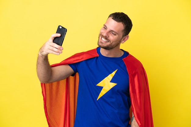 셀카를 만드는 노란색 배경에 고립 된 슈퍼 영웅 브라질 남자