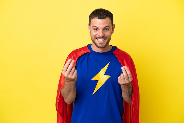 Бразильский человек супергероя изолирован на желтом фоне, делая денежный жест