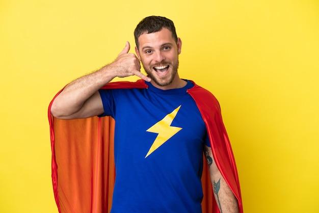 Бразильский человек супергероя, изолированные на желтом фоне, делая телефонный жест. перезвони мне знак