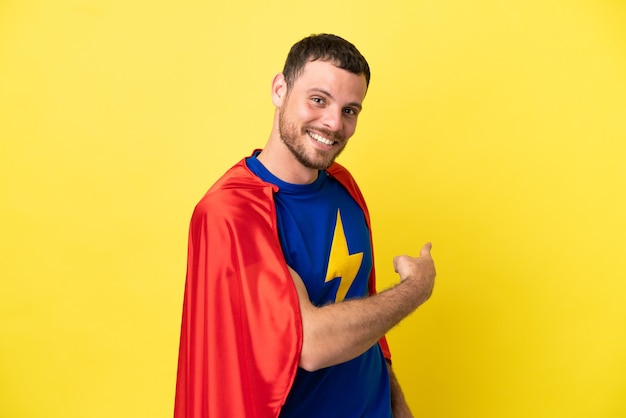 Бразильский человек супергероя изолирован на желтом фоне, указывая назад