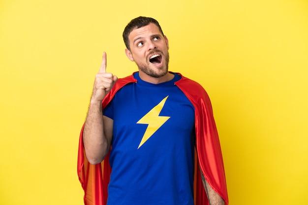 Супергерой бразильский мужчина изолирован на желтом фоне, указывая вверх и удивлен
