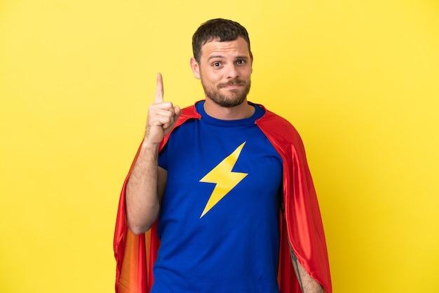 검지 손가락으로 가리키는 노란색 배경에 고립된 슈퍼 히어로 브라질 남자 좋은 아이디어
