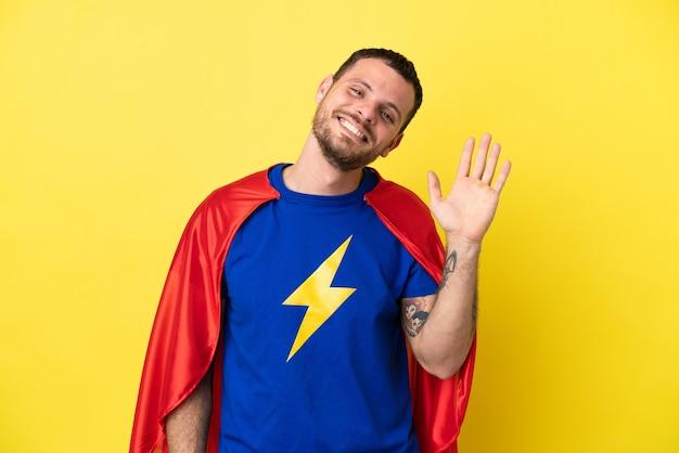 Супергерой бразильский мужчина изолирован на желтом фоне, салютуя рукой с счастливым выражением лица