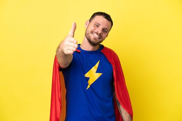 노란색 배경에 격리된 슈퍼 히어로 브라질 남자는 좋은 거래를 성사시키기 위해 악수를 하고 있다