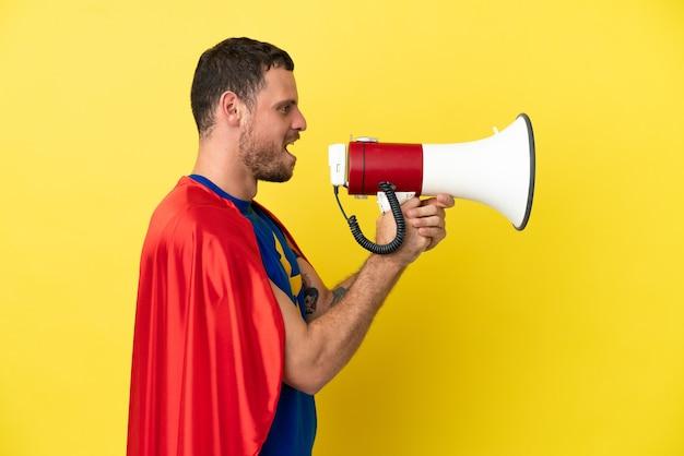 Супергерой бразильский человек, изолированные на желтом фоне, кричит через мегафон