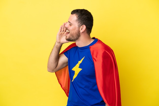 Супергерой бразильский мужчина изолирован на желтом фоне и кричит с широко открытым ртом