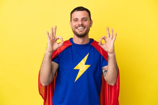 손가락으로 확인 표시를 보여주는 노란색 배경에 고립 된 슈퍼 영웅 브라질 남자