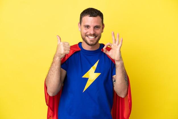 노란색 배경에 격리된 슈퍼 히어로 브라질 남자는 확인 표시와 엄지손가락 제스처를 보여줍니다.
