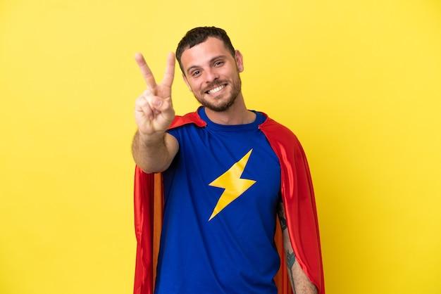 Бразильский человек супергероя изолирован на желтом фоне, улыбаясь и показывая знак победы