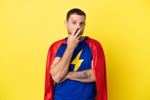 黄色の背景に分離されたスーパーヒーローのブラジル人男性は、右を見ながら驚いてショックを受けました