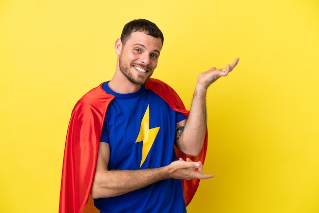 Super hero brazilian man isolated on yellow background extending hands to the side for inviting to come