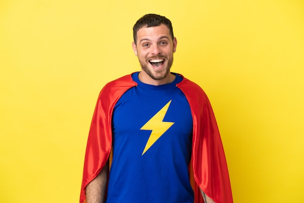 Super hero brazilian man isolated on yellow background with surprise facial expression