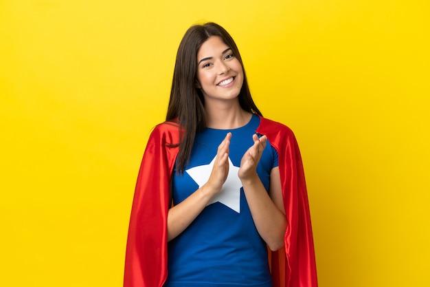 Супергерой бразильская женщина изолирована на желтом фоне аплодирует после презентации на конференции