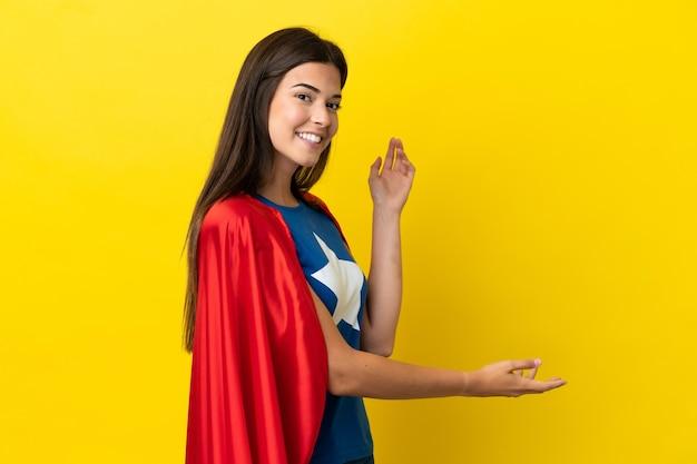 Супергерой бразильская женщина изолирована на желтом фоне, протягивая руки в сторону, приглашая приехать