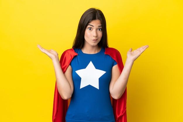手を上げている間疑いを持って黄色の背景に分離されたスーパーヒーローブラジル人女性