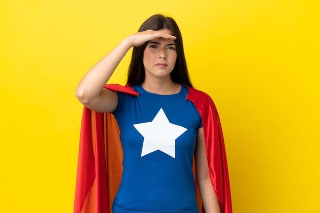 Супергерой бразильская женщина изолирована на желтом фоне, глядя далеко рукой, чтобы что-то посмотреть