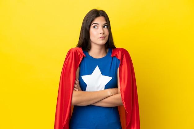 Супергерой бразильская женщина изолирована на желтом фоне, делая жест сомнения, поднимая плечи