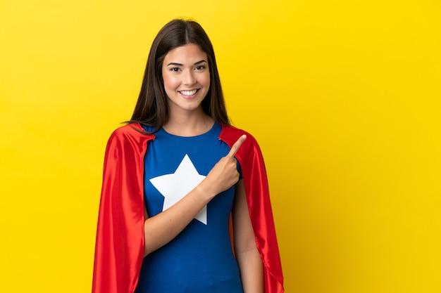 Супергерой бразильская женщина изолирована на желтом фоне, указывая в сторону, чтобы представить продукт