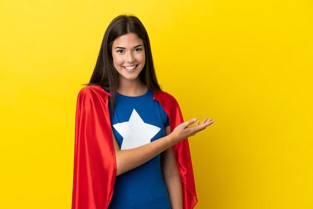 노란색 배경에 격리된 슈퍼 히어로 브라질 여성은 미소를 바라보면서 아이디어를 제시합니다.