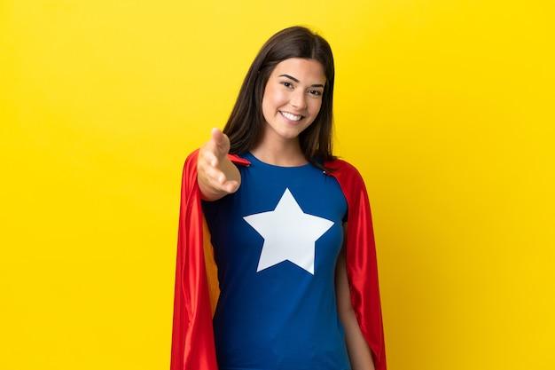 Супергерой бразильская женщина изолирована на желтом фоне, пожимая руку для заключения хорошей сделки