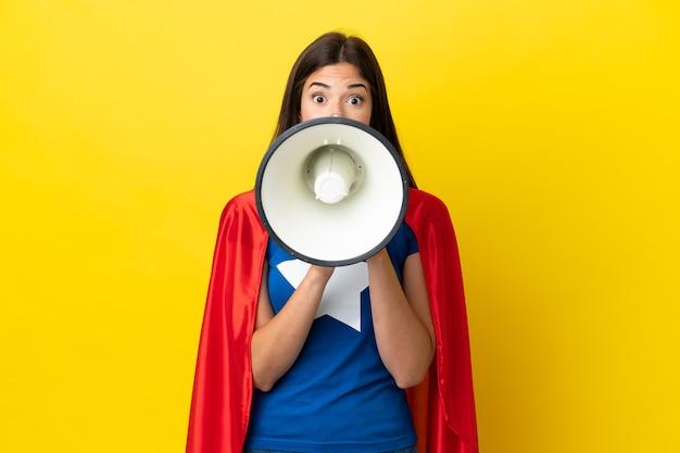 Супергерой бразильская женщина изолирована на желтом фоне кричит через мегафон