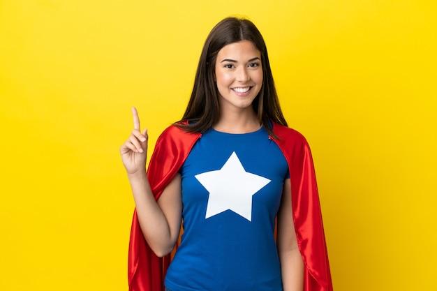 Супергерой бразильская женщина изолирована на желтом фоне, показывая и поднимая палец в знак лучших