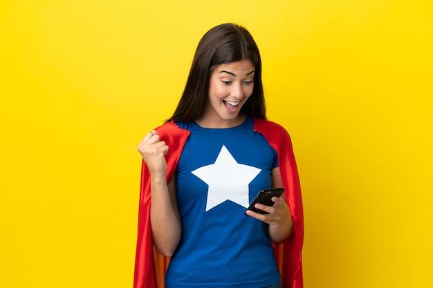 Супергерой бразильская женщина изолирована на желтом фоне удивлена и отправляет сообщение