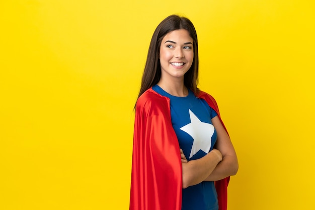 Супергерой бразильская женщина изолирована на желтом фоне со скрещенными руками и счастлива