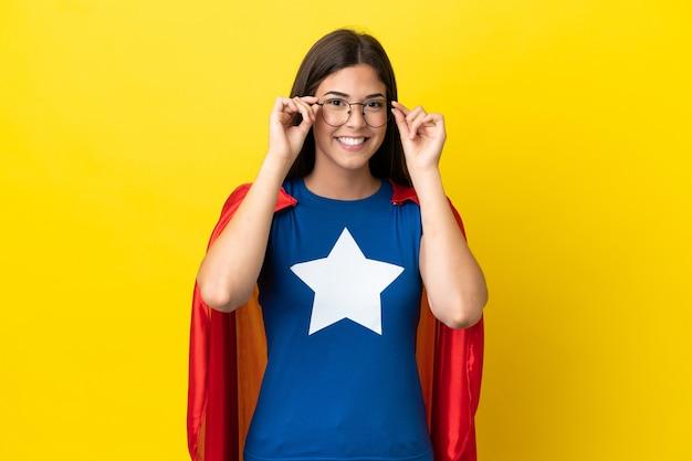 Супергерой бразильская женщина изолирована на желтом фоне в очках и удивлена