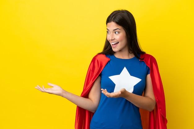 Супергерой бразильская женщина изолирована на желтом фоне с удивленным выражением лица