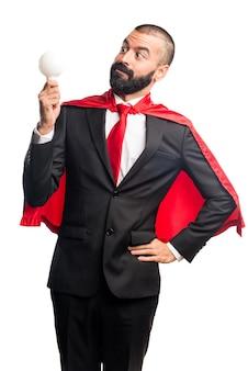 Супер герой бизнесмен держит лампочку