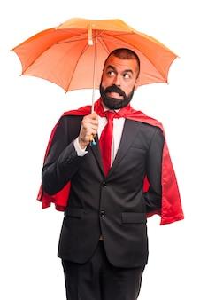Супер герой бизнесмен держит зонтик