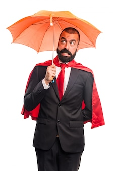 Super hero businessman holding an umbrella