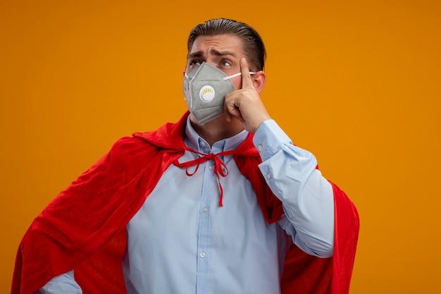オレンジ色の背景の上に立って困惑して脇を探している保護フェイシャルマスクと赤いマントのスーパーヒーローの実業家