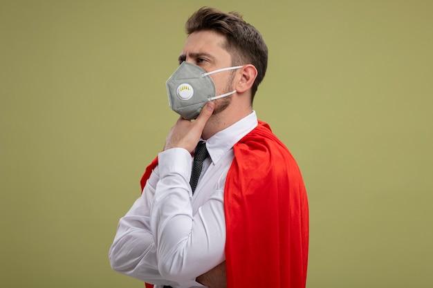 Бизнесмен супергероя в защитной маске для лица и красной накидке, глядя в сторону, положив руку на подбородок, думает с серьезным взглядом, стоя на зеленом фоне