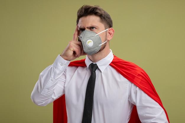 緑の背景の上に立って考えている顔に手で物思いにふける表情で脇を見て保護顔マスクと赤いマントのスーパーヒーロービジネスマン