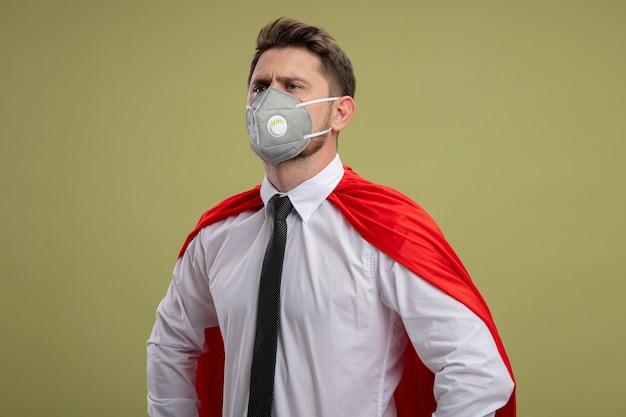 Бизнесмен супергероя в защитной маске для лица и красной накидке смотрит в сторону с серьезным уверенным выражением лица, стоя на зеленом фоне