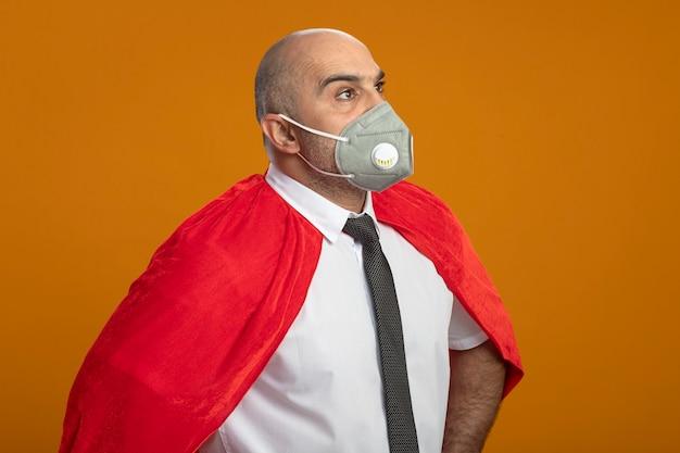 보호 얼굴 마스크와 오렌지 벽 위에 서 심각한 자신감 표정으로 제쳐두고 찾고 빨간 망토 슈퍼 영웅 사업가