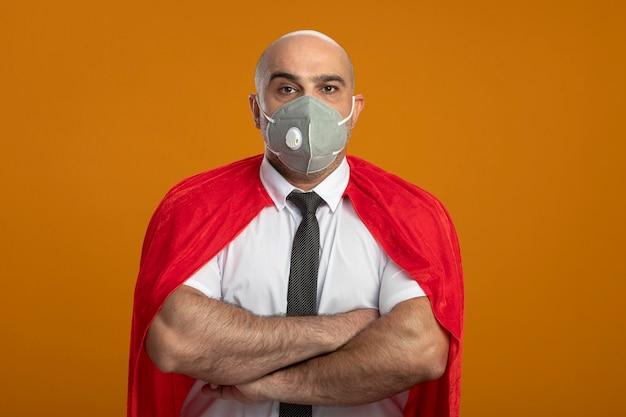 보호 얼굴 마스크와 빨간 망토의 슈퍼 영웅 사업가 오렌지 벽 위에 서 심각한 인상을 찌푸리고 얼굴로 가슴에 교차 손으로 정면을보고