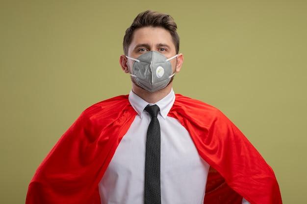 緑の壁の上に立っているヒップで腕に自信を持って見える保護フェイシャルマスクと赤いマントのスーパーヒーローのビジネスマン