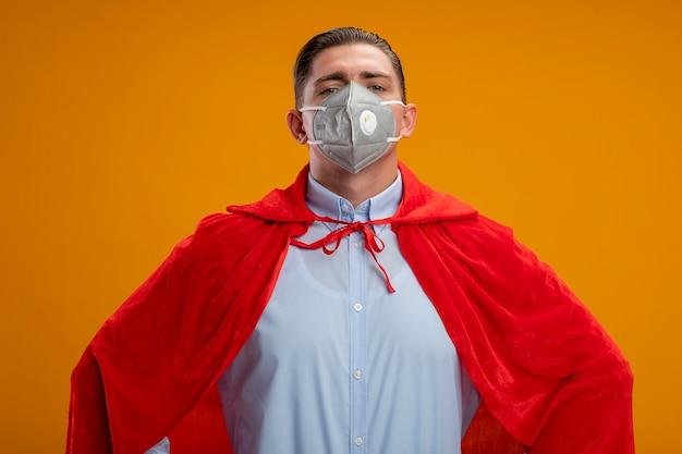 オレンジ色の壁の上に立っているヒップで腕に自信を持って見える保護フェイシャルマスクと赤いマントのスーパーヒーローのビジネスマン
